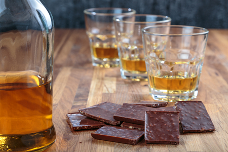chocolate and three glasses of whiskey on the oak surface of the table Reklamní fotografie - 95850668