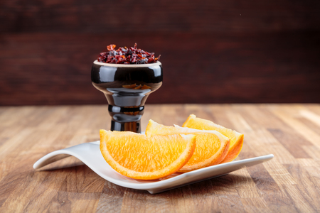shisha with apple flavor in a glossy black bowl, cooked for smoking, stands on a tray with three juicy slices of orange Stockfoto