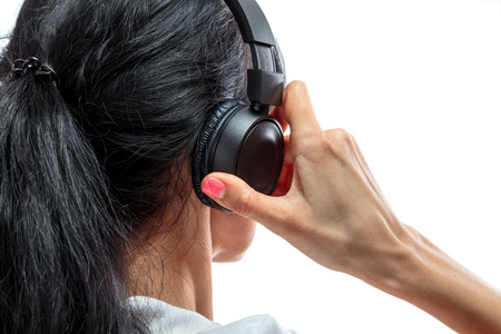 wireless headphones are on the head of a young girl brunettes with long hair