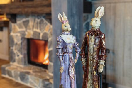 toy miniature figures of rabbits in the image of a lady and gentleman in an old clothes on the background of a vintage interior