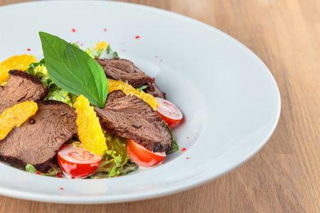 slices of boiled beef with lettuce, cherry tomatoes and orange pulp on a plate stand on an oak table
