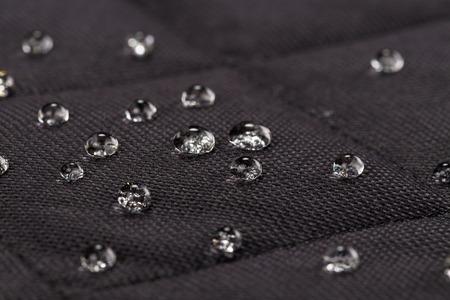 Water drops on waterproof black fabric. Macro photography.