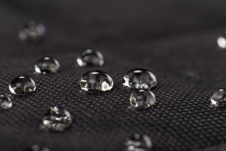 Gouttes d'eau sur tissu noir imperméable. Macrophotographie.