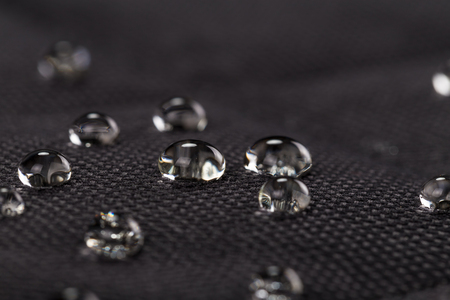 Water drops on waterproof black fabric. Macro photography.