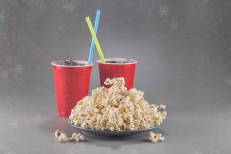 Closeup popcorn on the background of red plastic cups with fizzy drink with colored straws. Winter picture with snow.