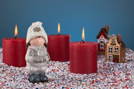 Three burning candles on the background of Christmas snowfall and toy figures. Merry Christmas and happy holidays Christmas story concept.