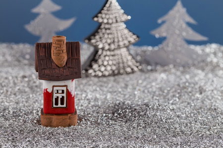 Miniature toy house in the Christmas story against the snow. Christmas card, new year card.