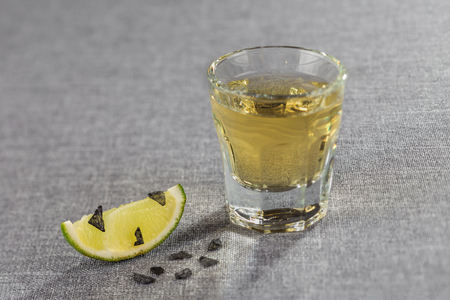 Close-up shot of Golden tequila with a slice of lime and black salt. Diagonal sharpness.