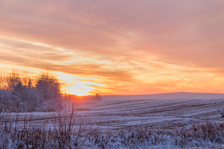 Beautiful winter sunset. The first snow in the fields at sunset.