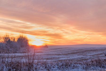Piękny zimowy zachód słońca. Pierwszy śnieg na polach o zachodzie słońca.