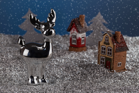 Porcelain Christmas deer on the background of miniature houses and fabulous new years landscape.. Christmas card, new year card.