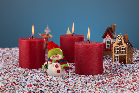 Three burning candles on the background of Christmas snowfall and toy figure snowman. Merry Christmas and happy holidays Christmas story concept. Stock Photo