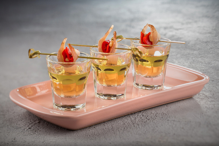 Close-up shot of three glasses of Golden tequila with tapas on skewers with dried meat, baked bell pepper and pine nuts.