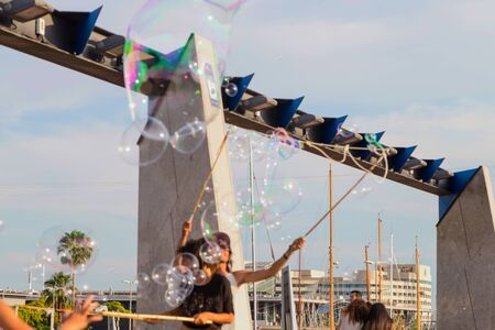 Soap bubble show on the pier in Barcelona, Spain, 28.06.2018. Happy children play outdoors in the background of moored yachts. Editorial