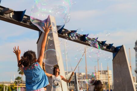 Soap bubble show on the pier in Barcelona, Spain, 28.06.2018. Girl jumping among soap bubbles.