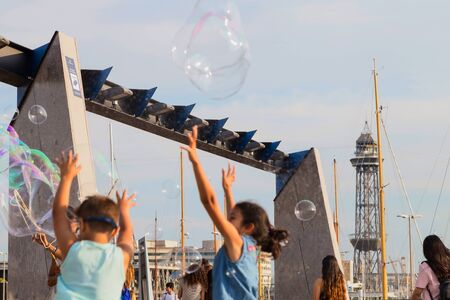 Soap bubble show on the pier in Barcelona, Spain, 28.06.2018. Happy children play outdoors in the background of moored yachts. Imagens - 128783135