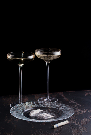 Cocaine on a plate, prepared for consumption, rolled into a tube 20 euros bill and a glases of champagne on a thin high leg. An idle existence. Copy space.