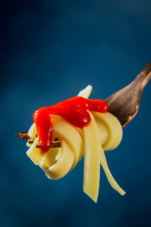 Spaghetti with ketchup on a fork on a beautiful colored background. Selective focus. Imagens