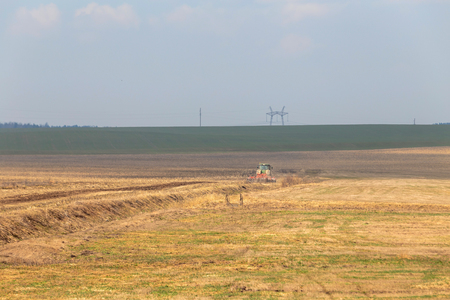 tractor plows the field in early spring for sowing crops. Agriculture of Belarus. Land cultivation.