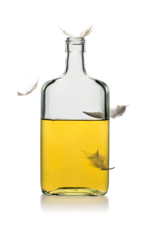Incomplete bottle of whiskey rectangular shape without lid with flying feathers isolated on white background. Vertical.