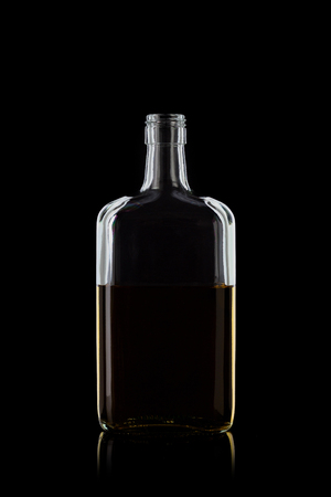 Bottle of whiskey rectangular shape, isolated on a black background with reflections. 100 sharpness. Vertical.