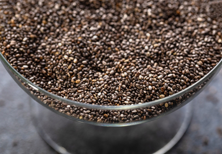 Chia seeds in a glass vase close-up. The texture of the seeds. Horizontal. Stock Photo