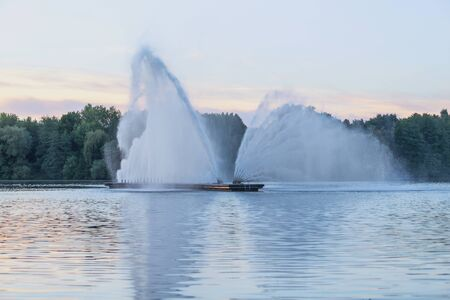 Fountain, beating powerful jets in the middle of the reservoir on the background of a beautiful sunset. Selective focus.