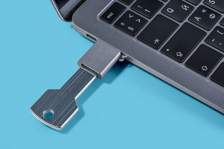 USB-drive in the form of a key through the adapter connected to a modern laptop on a blue background. Imagens