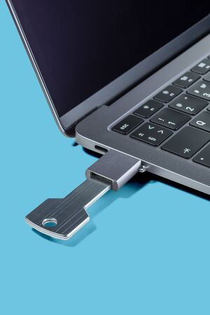 USB-drive in the form of a key through the adapter connected to a modern laptop on a blue background. Imagens - 128615672