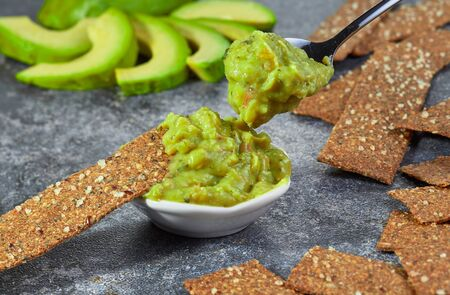 Guacamole in a bowl on a background of sliced avocado. Horizontal. Imagens
