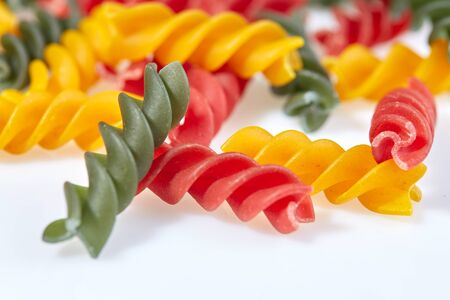 Pasta in the form of spirals of different colors on a white surface close-up. Imagens