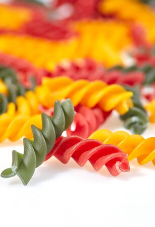 Pasta in the form of spirals of different colors on a white surface close-up. Imagens - 128615681