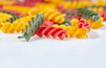 Pasta in the form of spirals of different colors on a white surface close-up. Reklamní fotografie