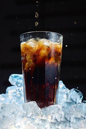 Glass of soda with ice on a dark background. Carbonated beverages.