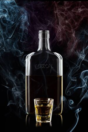 Bottle of mescal and a glass of mescal, isolated on a black background with smoke and reflections. 100 sharpness. Vertical.
