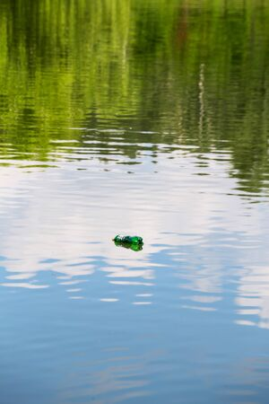 Empty plastic bottle floats on the calm surface of the pond with beautiful reflections of clouds and trees.
