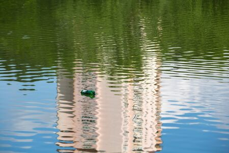 Empty plastic bottle floats on the calm surface of the pond with beautiful reflections of clouds, houses and trees. Reklamní fotografie