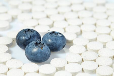Three ripe blueberries are surrounded by pills on all sides. Concept: natural vitamins. Close up.