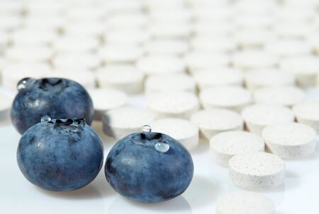 Three ripe blueberries on a background of tablets spread out on a light surface. Concept: natural vitamins. Selective focus. Reklamní fotografie
