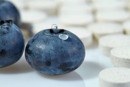 Three ripe blueberries on a background of tablets spread out on a light surface. Concept: natural vitamins.