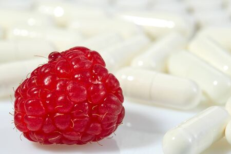 Ripe raspberry berry on the background of tablets lies on a light surface. Concept: natural vitamins. Reklamní fotografie