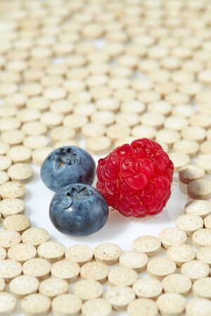 Ripe raspberries and blueberries are surrounded by pills on all sides. Concept: natural vitamins Reklamní fotografie