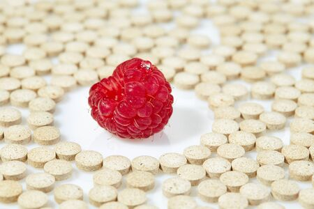 Ripe raspberries surrounded by pills on all sides. Concept: natural vitamins. Reklamní fotografie