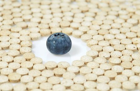 Ripe blueberries surrounded by pills on all sides. Concept: natural vitamins.