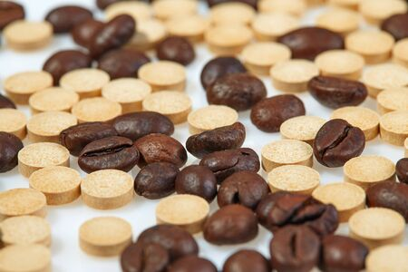 Coffee beans mixed with caffeine tablets are scattered on a light surface.