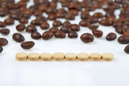 Tablets are laid out in a horizontal row on a white surface against the background of coffee beans.