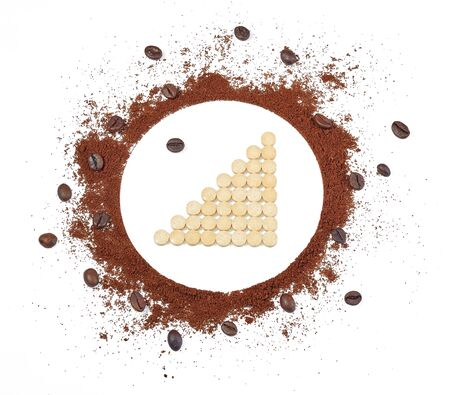 Tablets laid out in the form of a graph of positive growth inside the circle of ground coffee and coffee beans, isolated on a white background. Isolated.