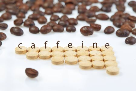 Tablets are laid out in ascending order of dose on a white surface with the inscription CAFFEINE on the background of coffee beans.