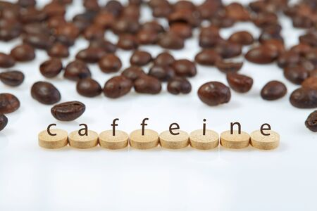Tablets laid out in a horizontal row on a white surface with the inscription CAFFEINE on the background of coffee beans. Horizontal