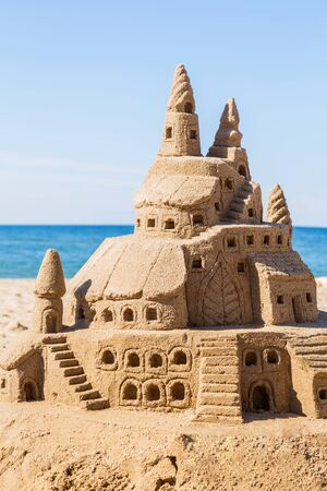 Sand castle on the beach, against the sea and sky. Concept: unrealized dreams.